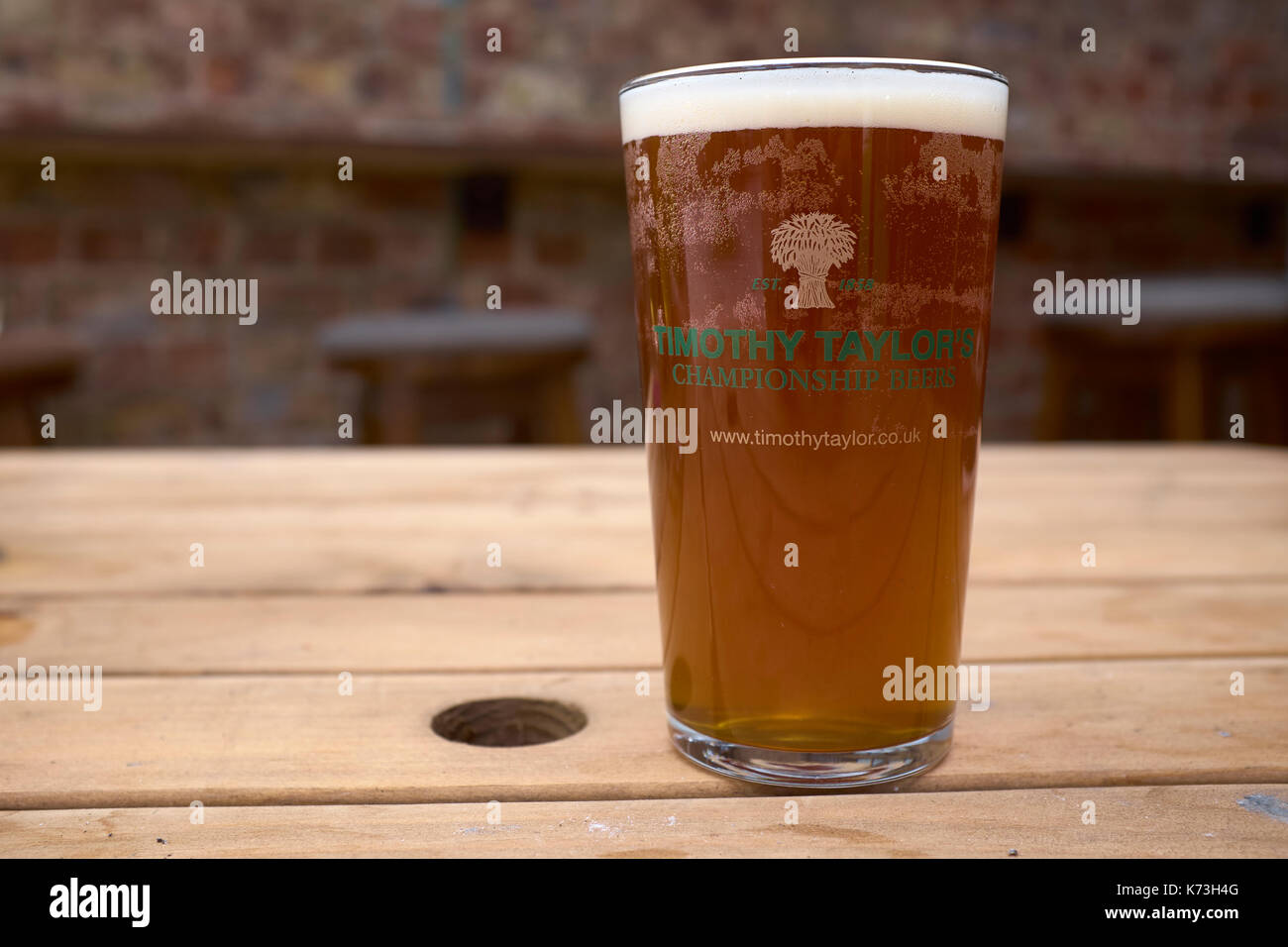 Pint of Timothy Taylor's bitter on a wooden table, Yorkshire, United Kingdom - Stock Image