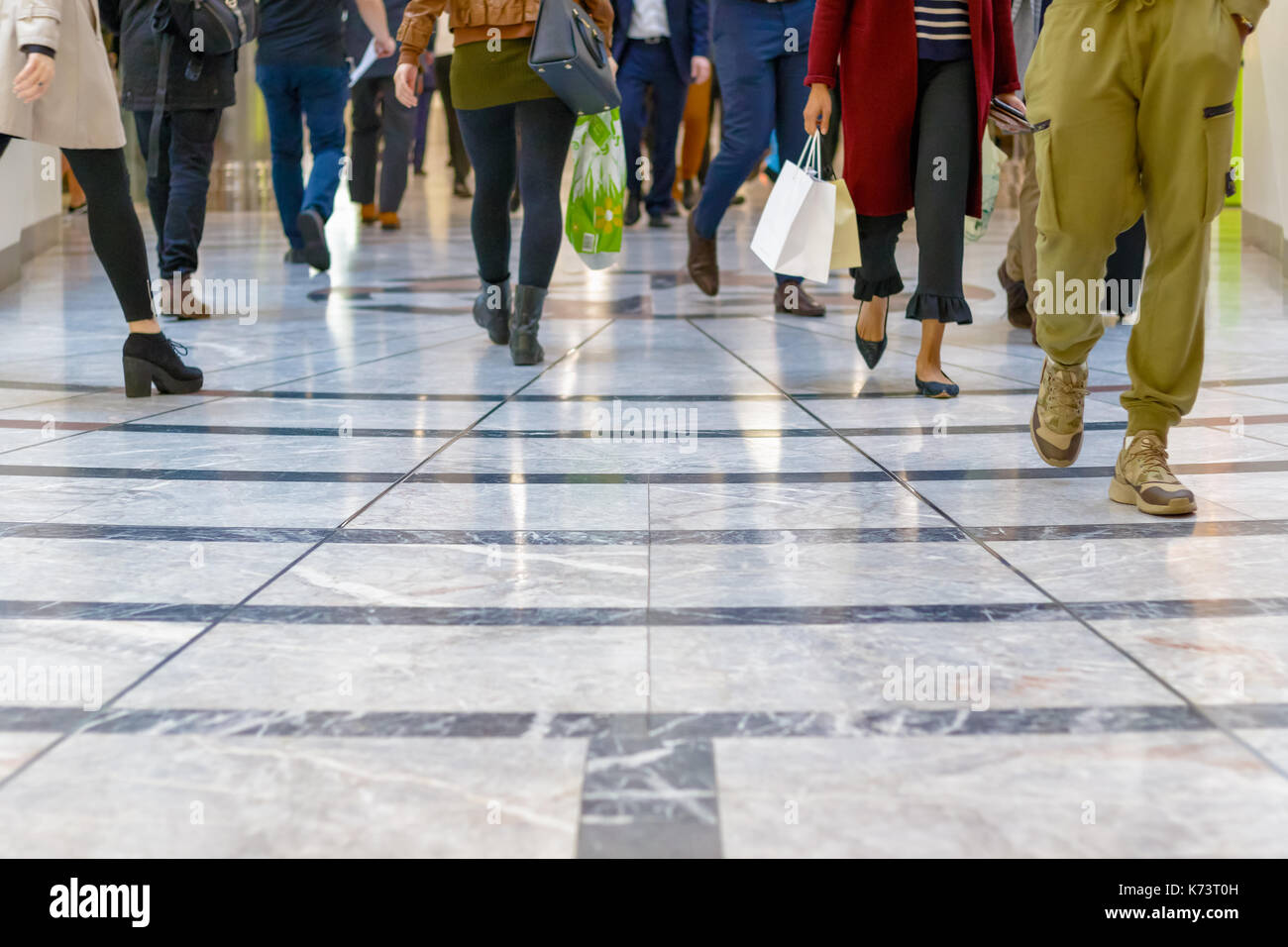 A modern floor with legs of a crowd walking in a shopping mall in the background - Stock Image