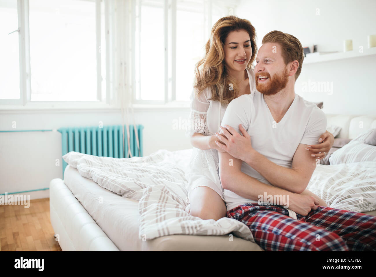 Beautiful happy couple waking up smiling in bedroom - Stock Image