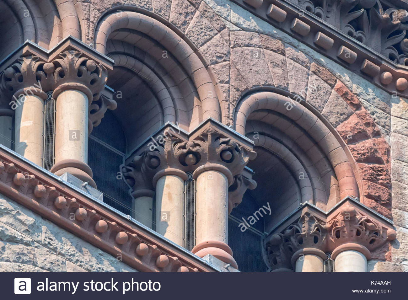 Old City Hall Richardsonian Romanesque Revival architectural details.Columns and arches in windows.  The red stone old building is a tourist attractio - Stock Image