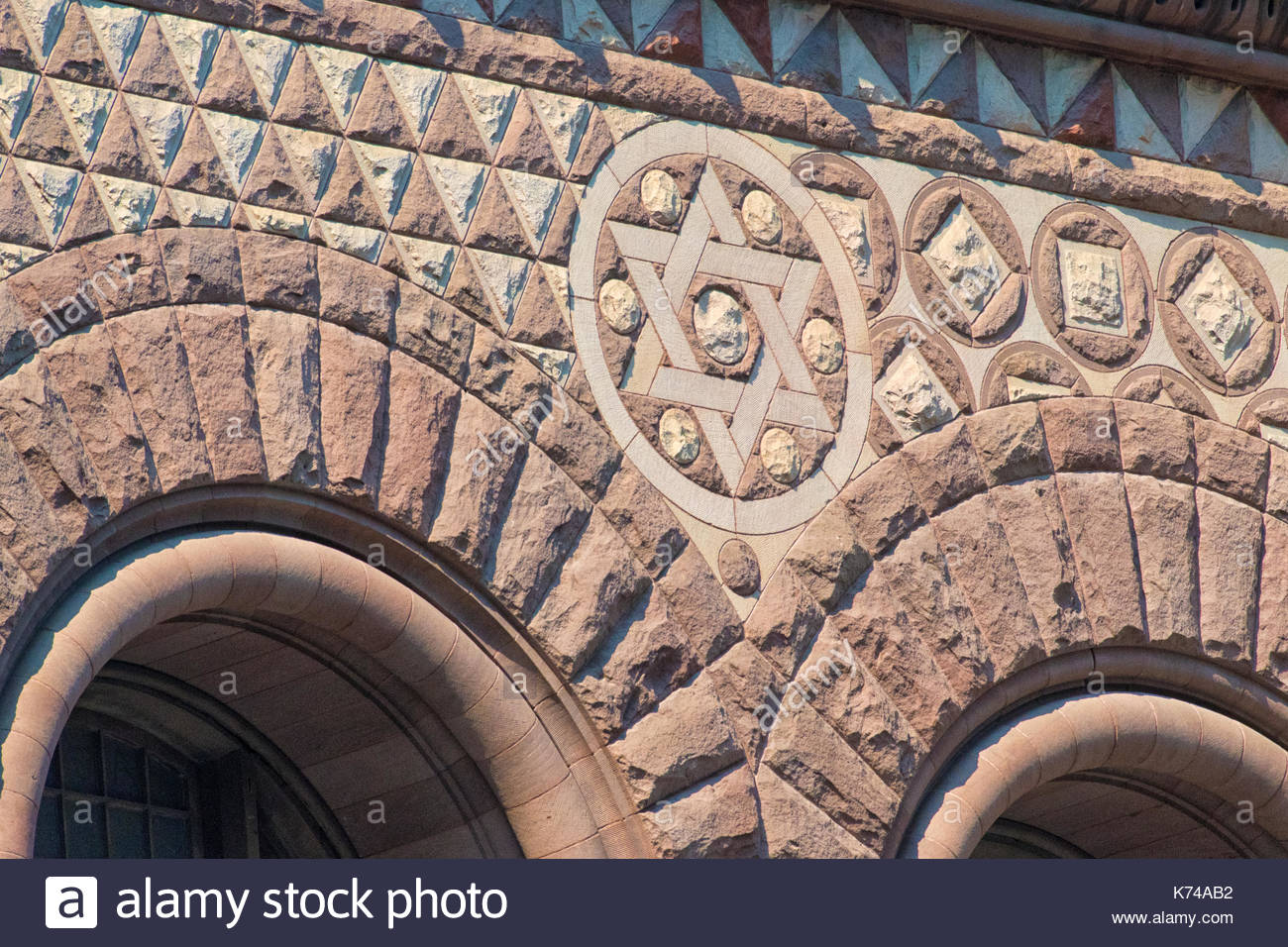 Old City Hall Richardsonian Romanesque Revival architectural details. David star and arches in the facade.  The red stone old building is a tourist at - Stock Image