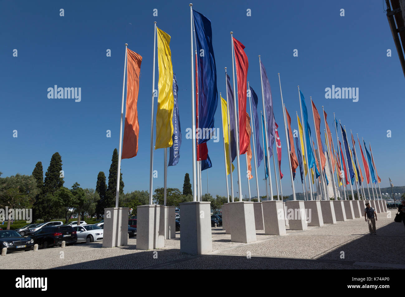 An array of brightly coloured flags flying from flag poles outside the cultural centre Lisbon Portugal - Stock Image