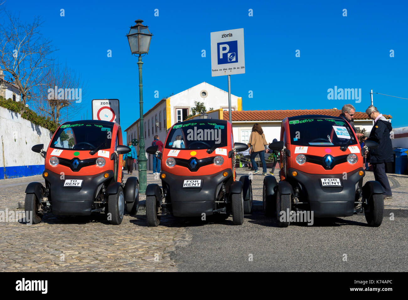 A row of parked Renault Twizy electric cars for rent in Obidos Portugal Stock Photo