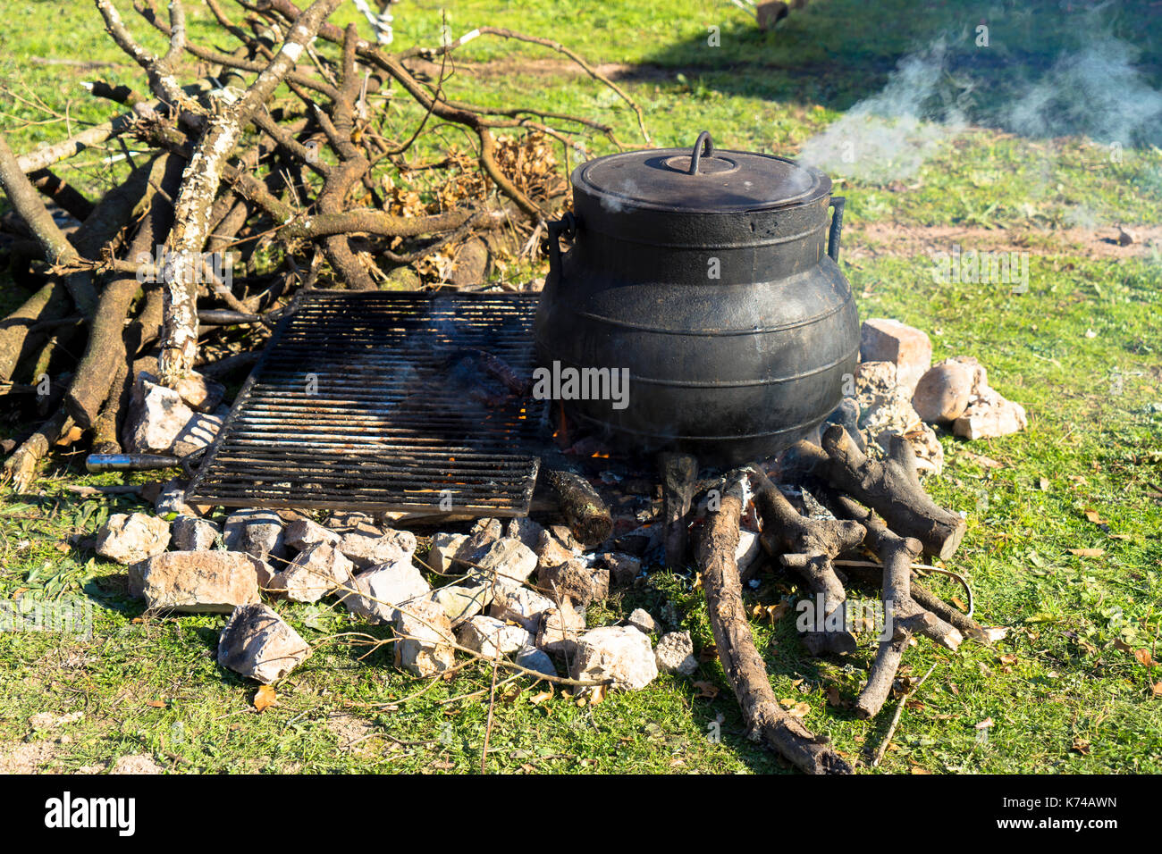 Cooking over an open fire using a metal cooking pot gently steaming on a wood burning campfire - Stock Image