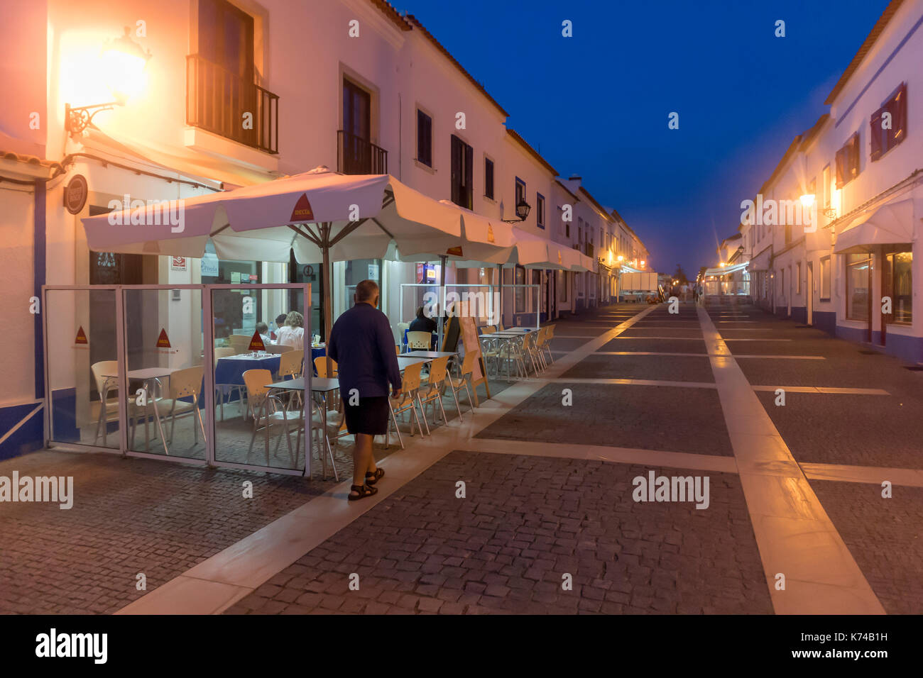 Man walking past a restaurant in a quiet brightly lit paved street of Porto Covo, Setubal, Portugal - Stock Image