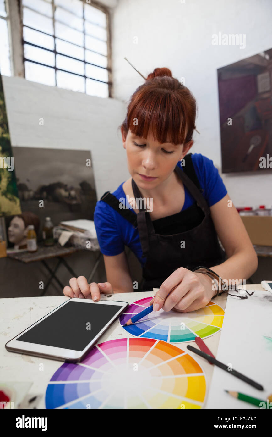 Beautiful woman matching color with color swatch at table - Stock Image