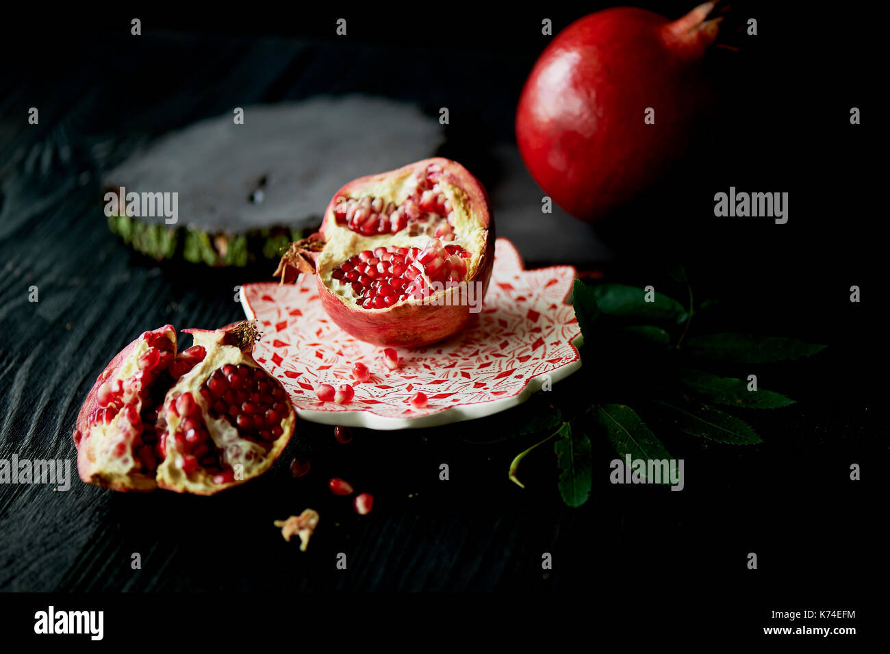 Useful antioxidant pomegranate, lies with the dark countertops. One in broken with juicy flesh.Framed by green leaves. Healthy eating during the vitamin deficiency - Stock Image