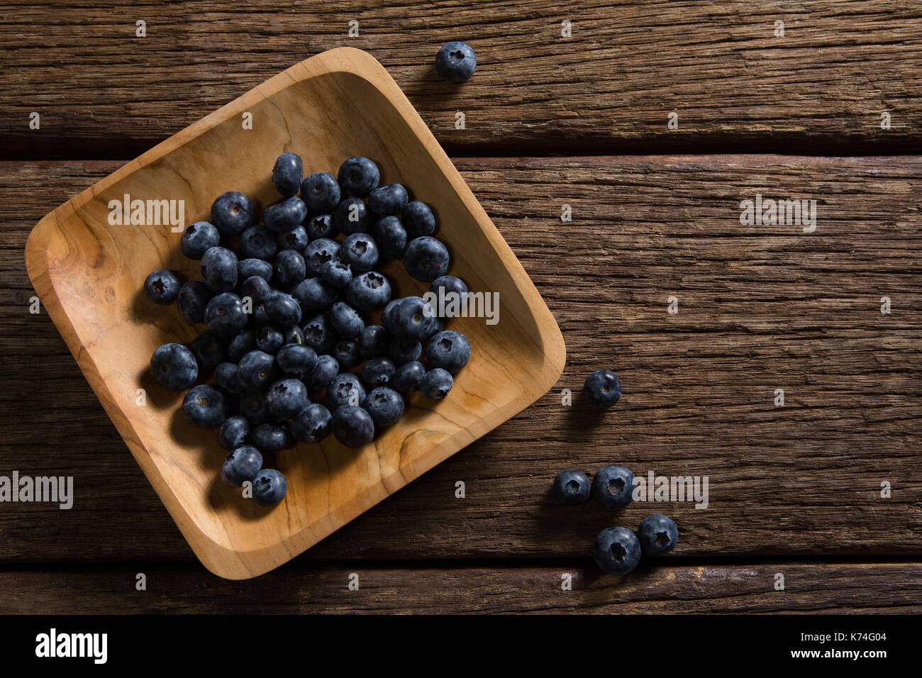 Plate of blueberries on wooden table - Stock Image