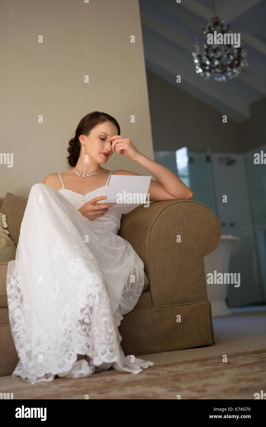033c380e4 Low angle view of beautiful bride reading wedding card while sitting on  sofa at home
