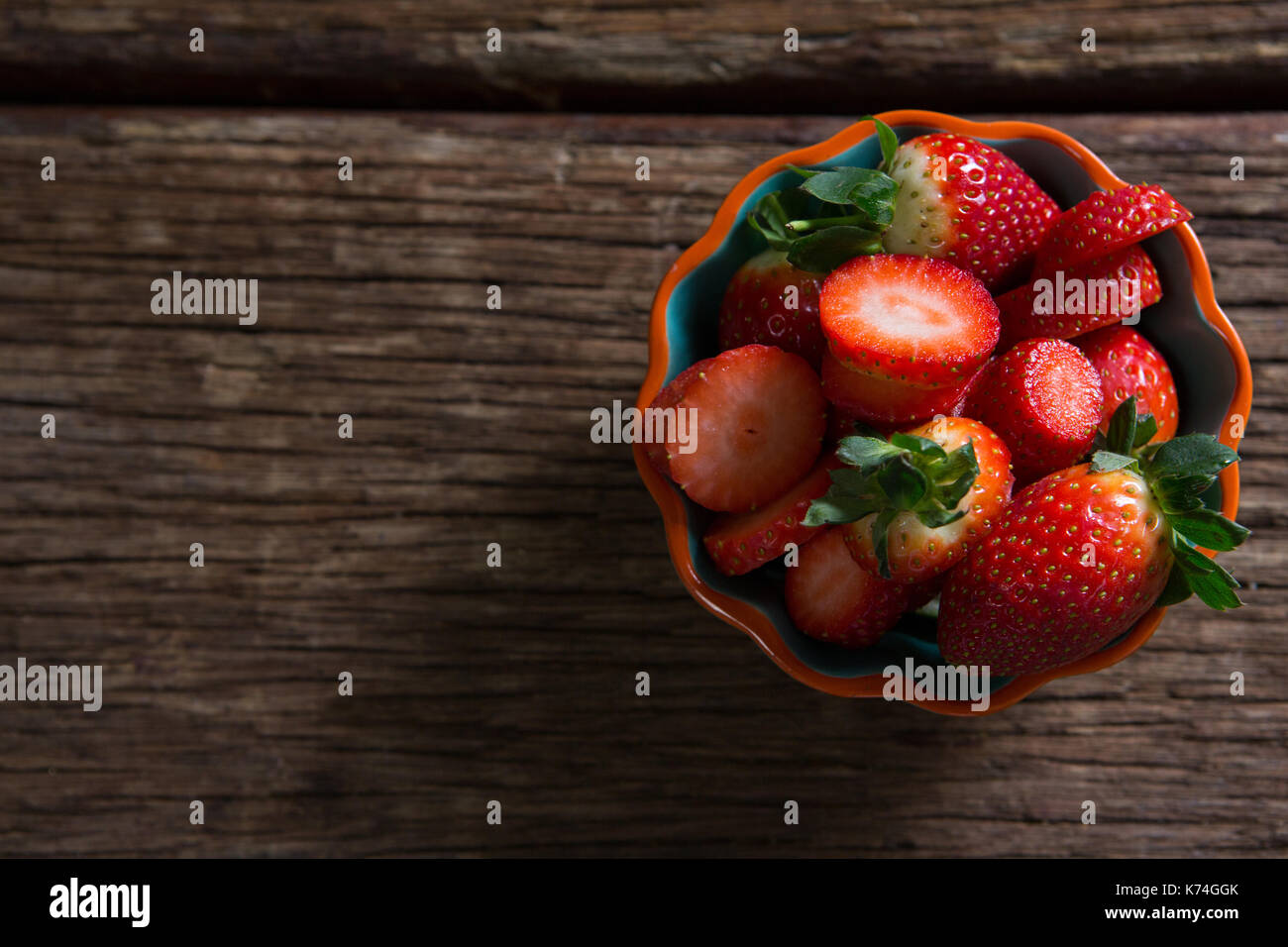 Bowl of strawberries on wooden table - Stock Image