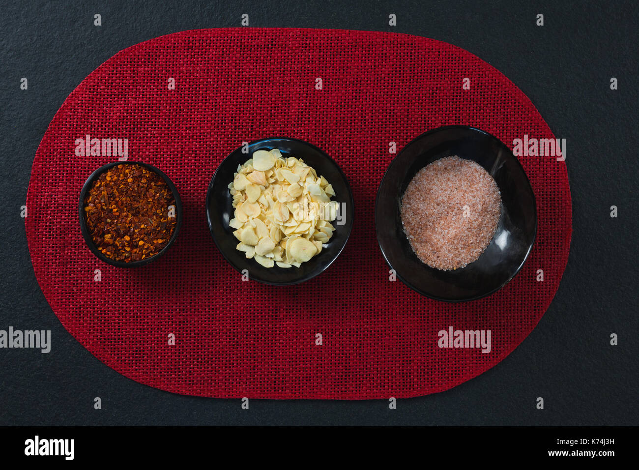 Red pepper flakes, roasted coconut chips and salt on a place mat - Stock Image