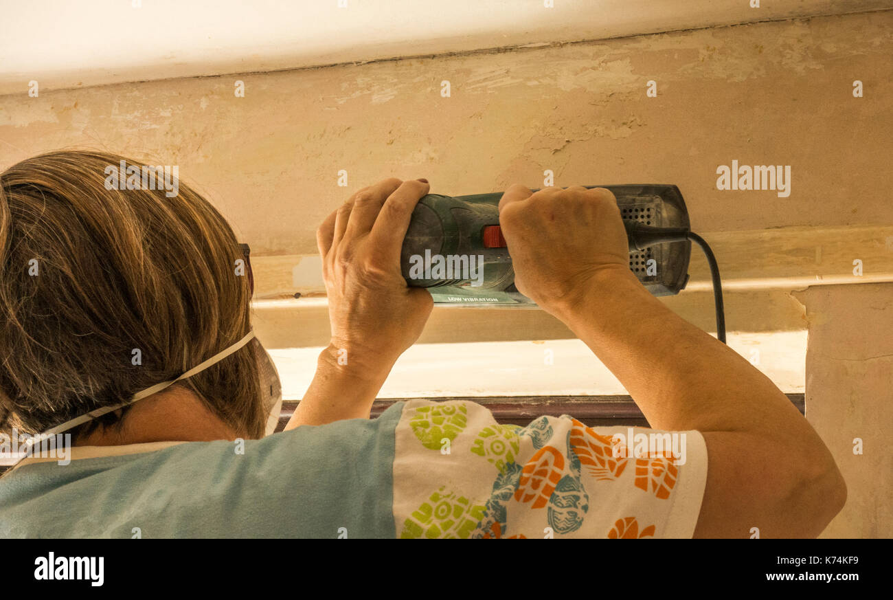 A woman wearing a dust mask on her face, while sanding wood with a power tool, in a room in her home she is decorating / redecorating. England, UK. - Stock Image