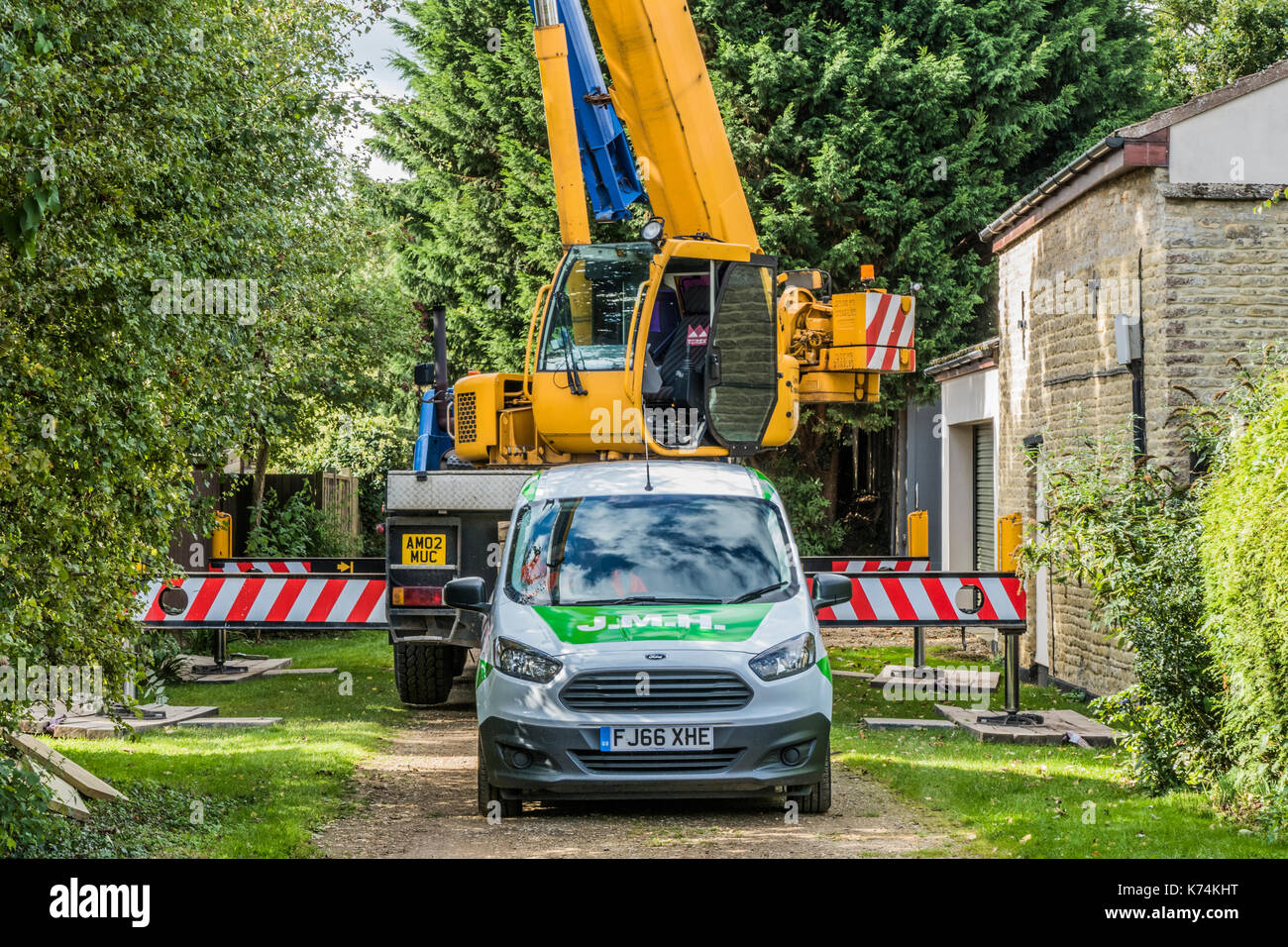 A large crane lorry and car parked in a back lane, on hire to lift heavy construction materials into a nearby garden. Lincolnshire, England, UK. - Stock Image