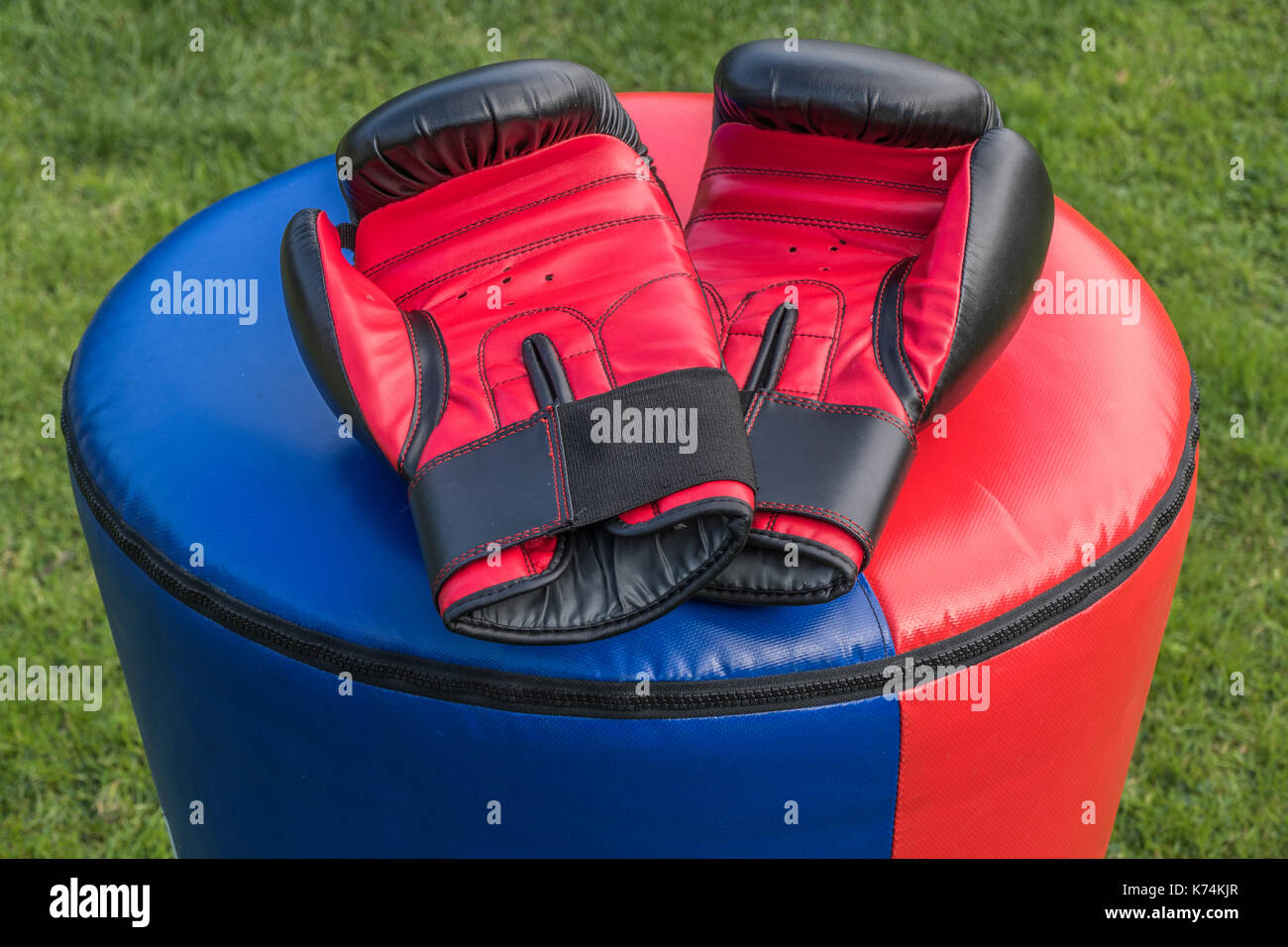 A pair of soft, padded, protective sparring gloves resting on a punchbag after a kickboxing fitness workout. Each glove is black and red. - Stock Image