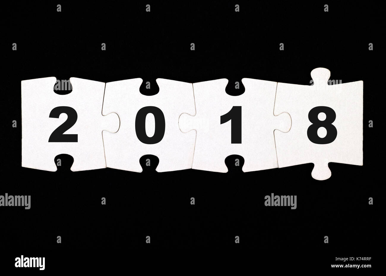 Four pieces of puzzle with numbers 2 0 1 8 are connected together on black background Stock Photo