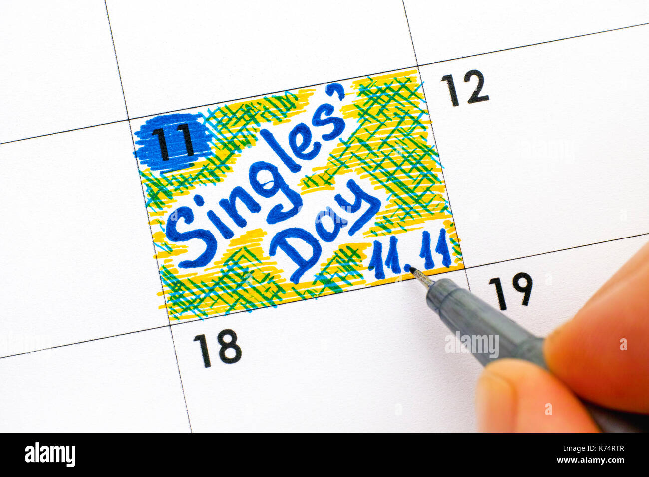 Woman fingers with pen writing reminder Singles Day 11.11 in calendar. Close-up. - Stock Image