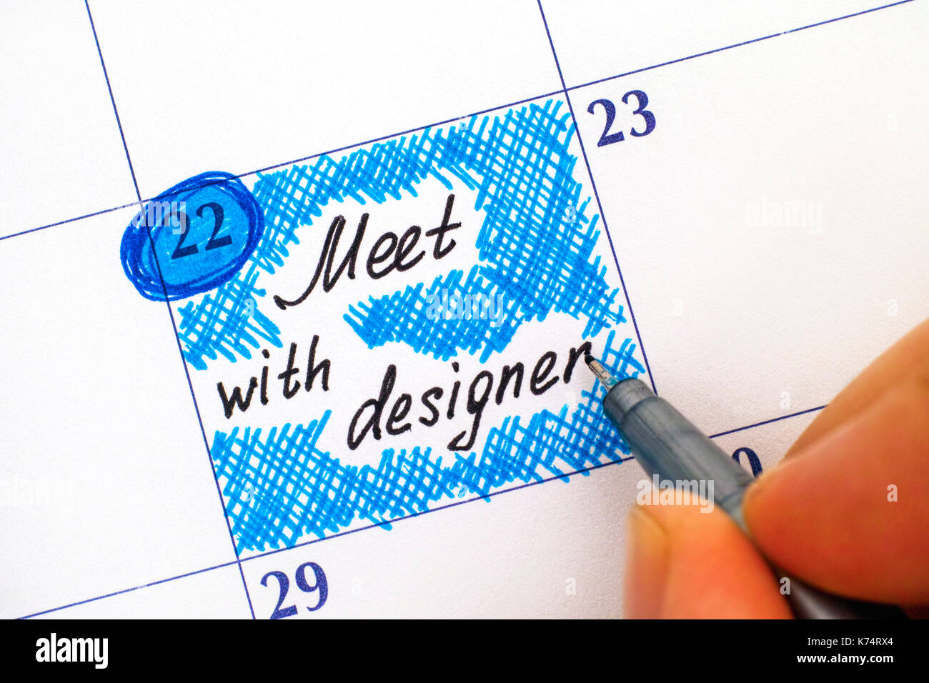 Woman fingers with pen writing reminder Meet with designer in calendar. Close-up. - Stock Image