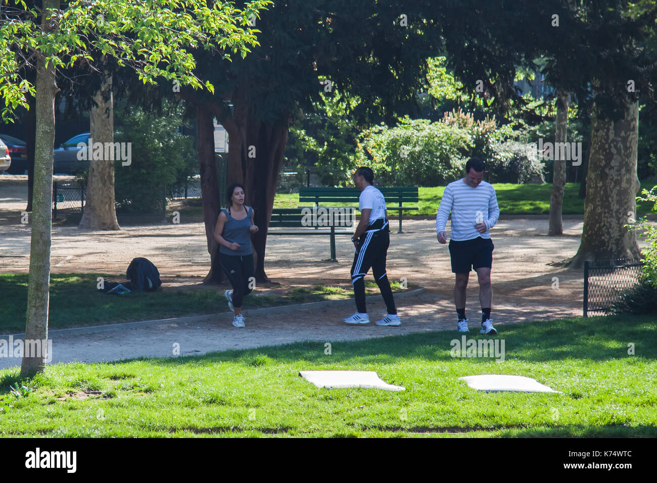 A group of people warming up for jogging in the park on a sunny day several days before The Paris International Marathon. Paris, France - Stock Image