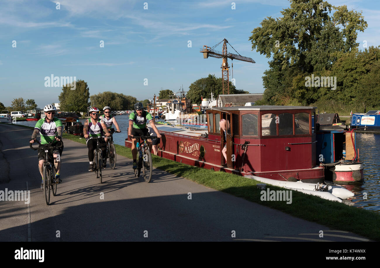 Gloucester & Stroudwater Canal at Saul Junction, Gloucestershire England UK. 2017. Group of male cyclists cycling on the towpath. - Stock Image
