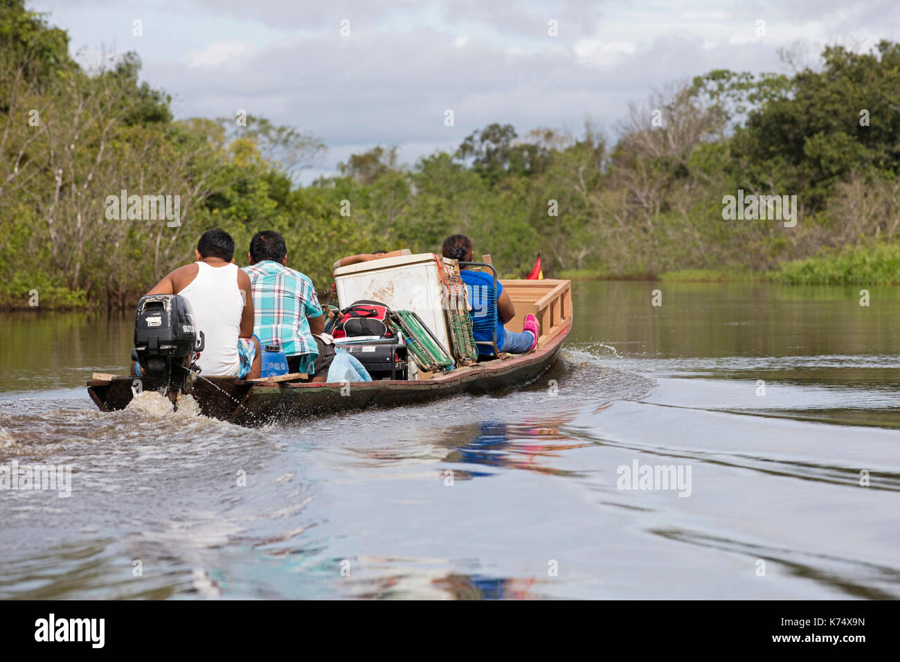 Local Bolivians moving furniture by canoe with outboard motor on the Yacuma River in the Pampas del Yacuma in Bolivia - Stock Image