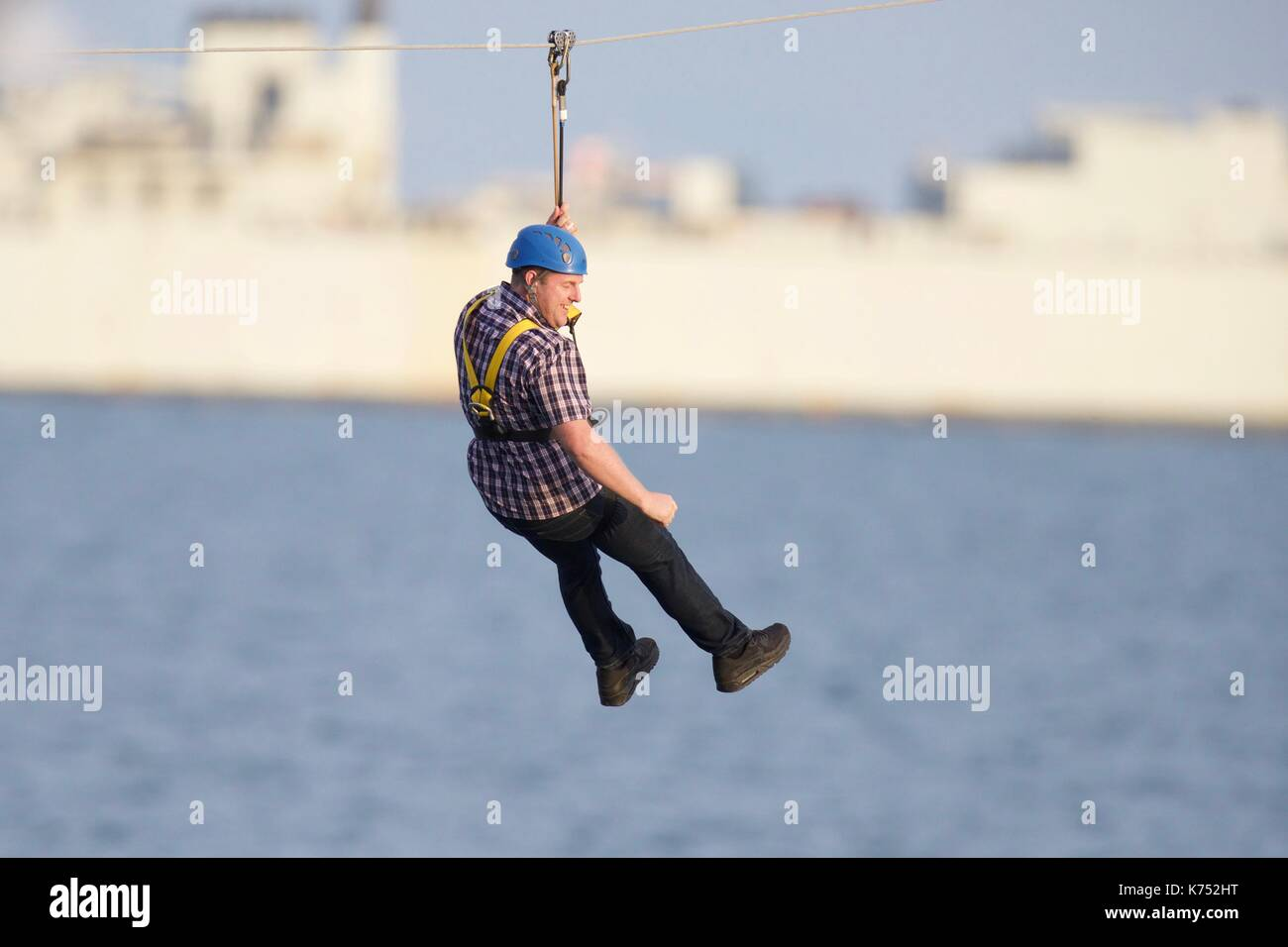 A man enjoying a thrill ride on the Bournemouth  pier to shore zip wire - Stock Image