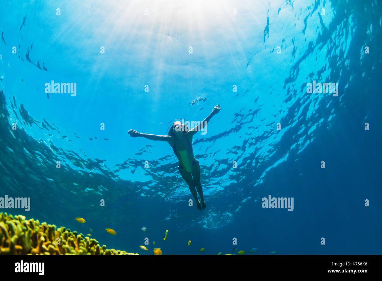 Happy family - girl dive underwater with tropical fishes in coral reef sea pool. Travel lifestyle, water sport outdoor adventure, swimming lessons. - Stock Image