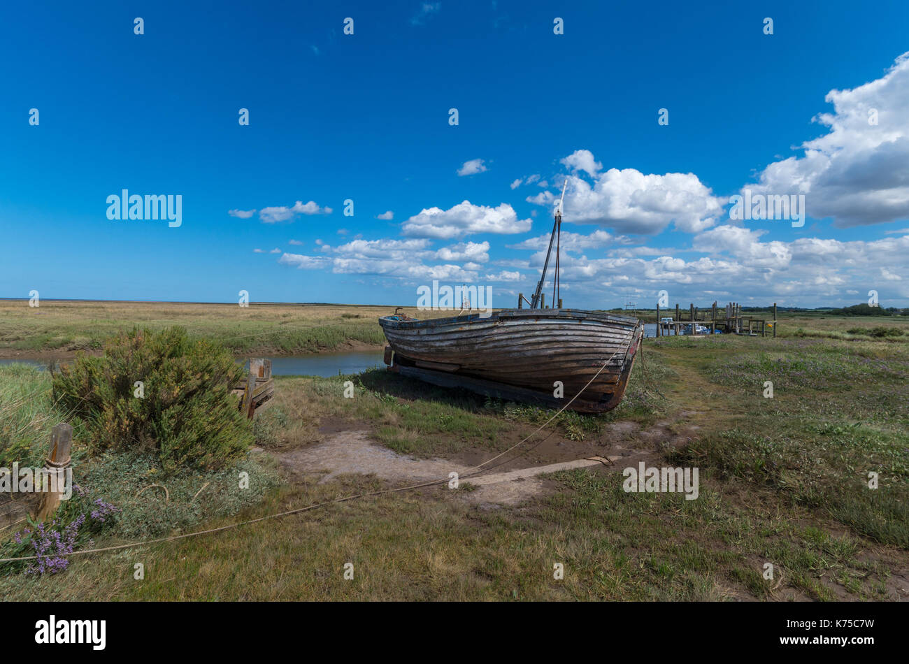 Wrecked boat on the tidal marshes at Thornham Harbour on the North Norfolk coast, UK. - Stock Image