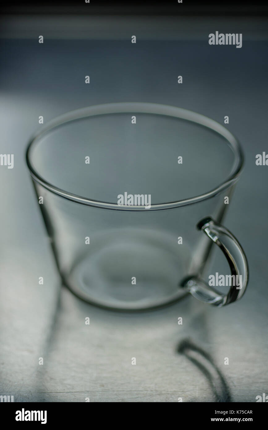Empty glass coffee cup on a stainless steel surface 14.09.2017 PHILLIP ROBERTS - Stock Image