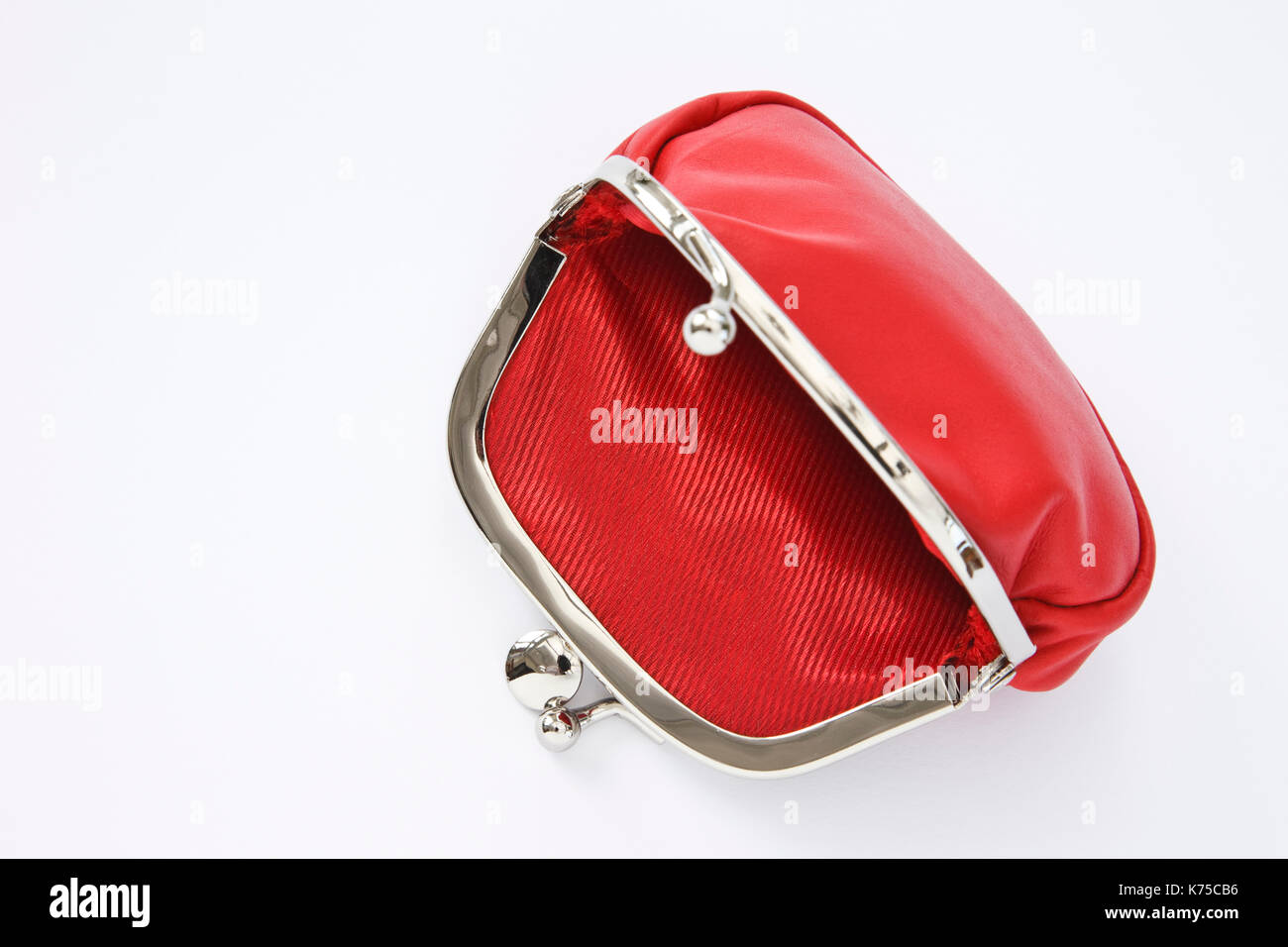 Empty red purse open to illustrate poverty and austerity concept. Isolated on a white background England, UK, Britain - Stock Image