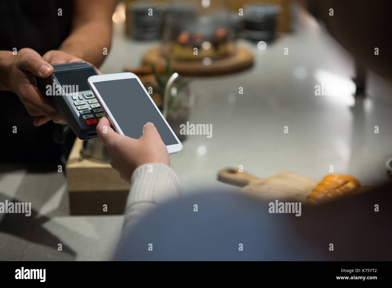 Woman paying bill through smartphone using NFC technology in restaurant Stock Photo