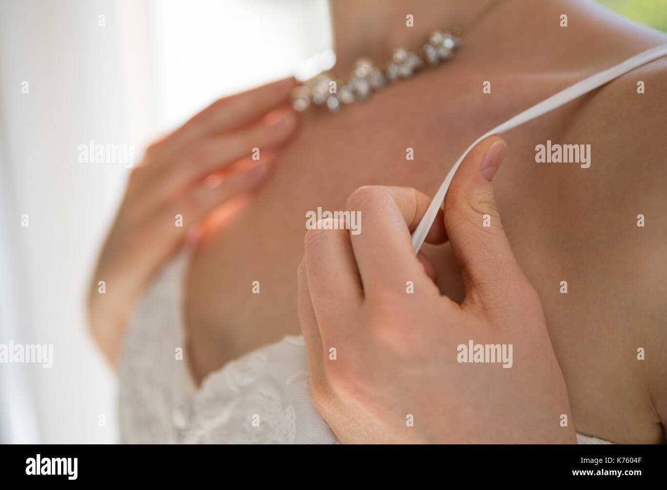 Midsection of bride in sleeveless wedding dress standing at home - Stock Image