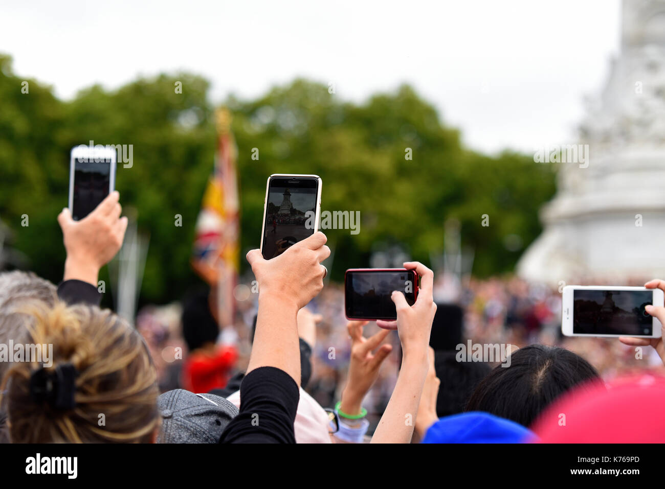 Quantity of mobile phone cameras raised to film and photograph the changing of the guard passing the Victoria Memorial in London, UK. Smart phones - Stock Image