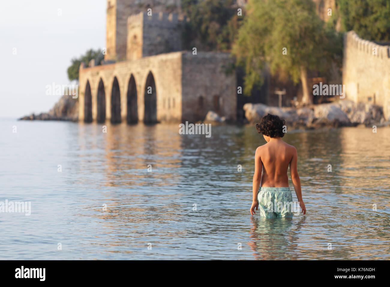 Backview of portrait of boy with dark hair wearing swimwear standing in water near Alanya medieval shipyard in mediterrarian sea - Stock Image