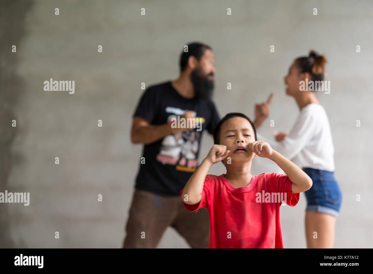 The concept of parental family quarrels, Young Couple Parents are fighting in front of children. - Stock Image