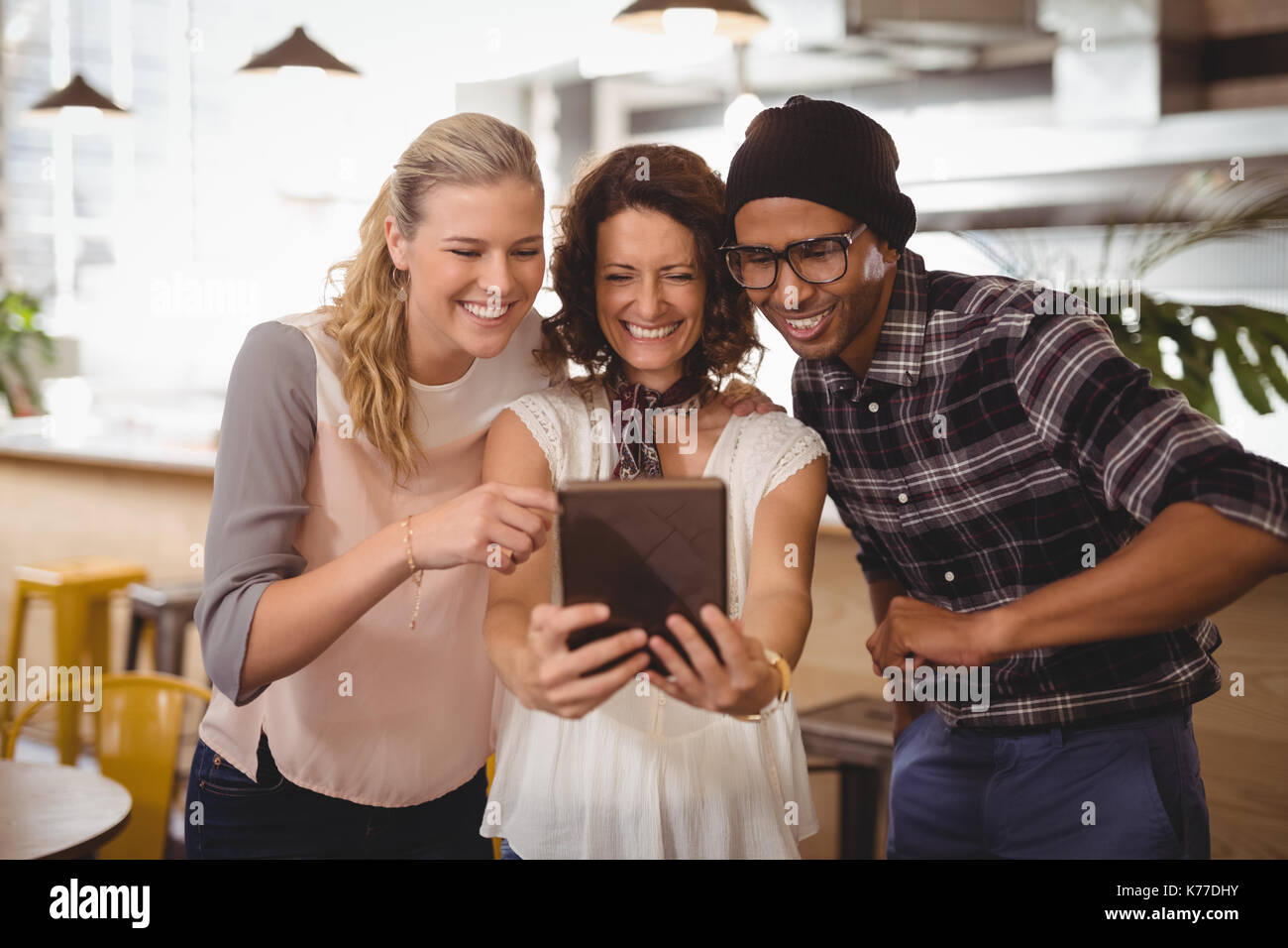 Cheerful multi ethnic friends taking selfie from digital tablet while standing at coffee shop - Stock Image