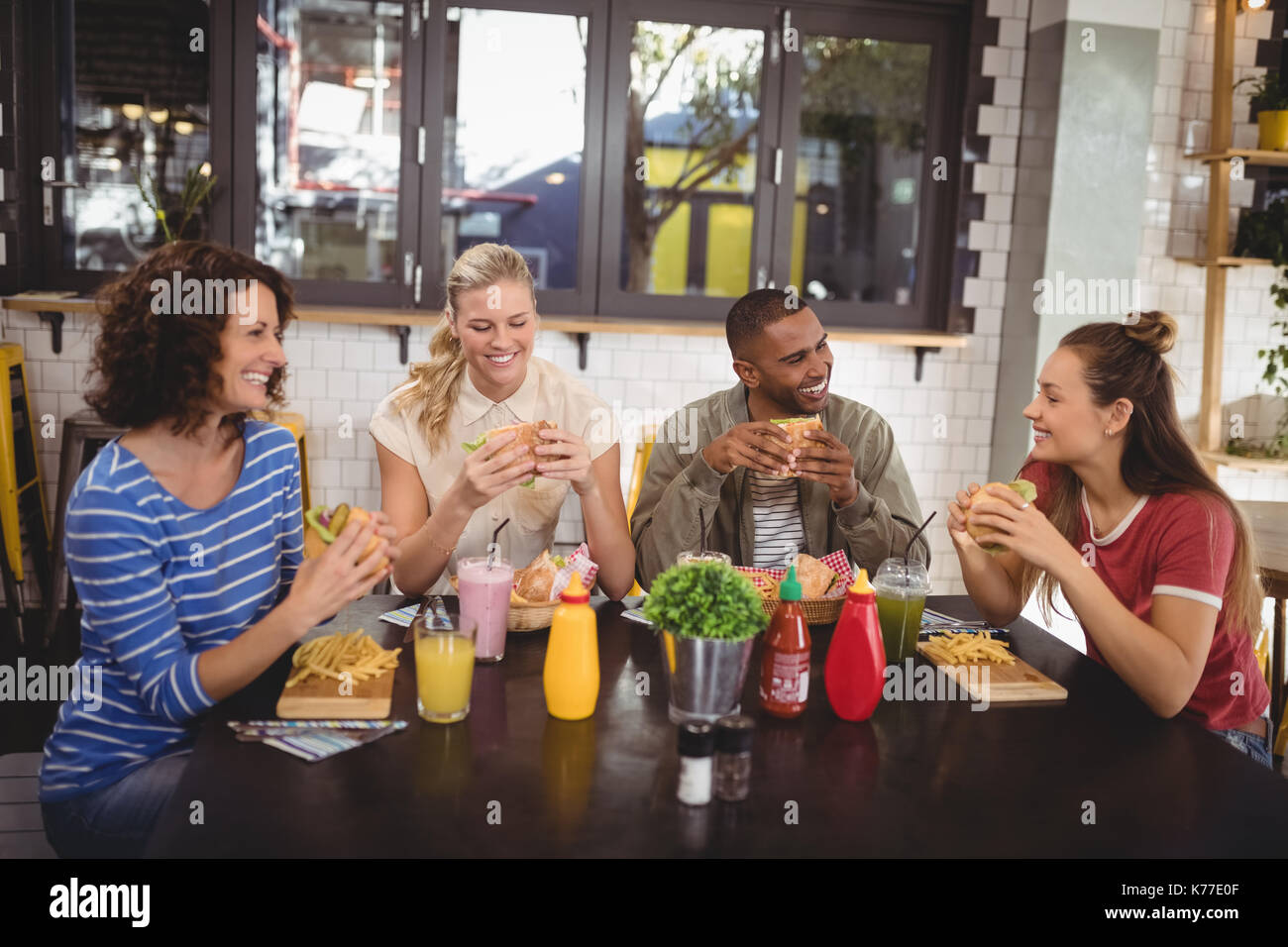 Smiling young friends eating food while sitting at table in coffee shop - Stock Image