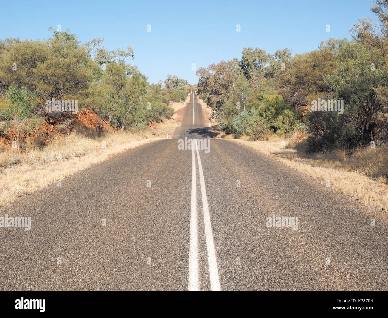 The hot bitumen road to the horizon at Larapinta Drive, west MacDonnell ranges near Alice Springs, Northern Territory, Australia 2017 - Stock Image