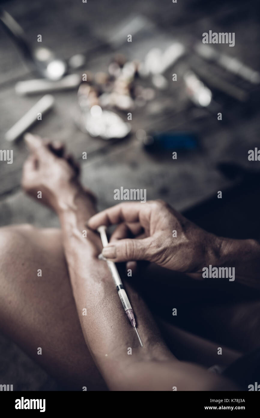 Drug addict young woman with syringe in action, Drug abuse concept. - Stock Image