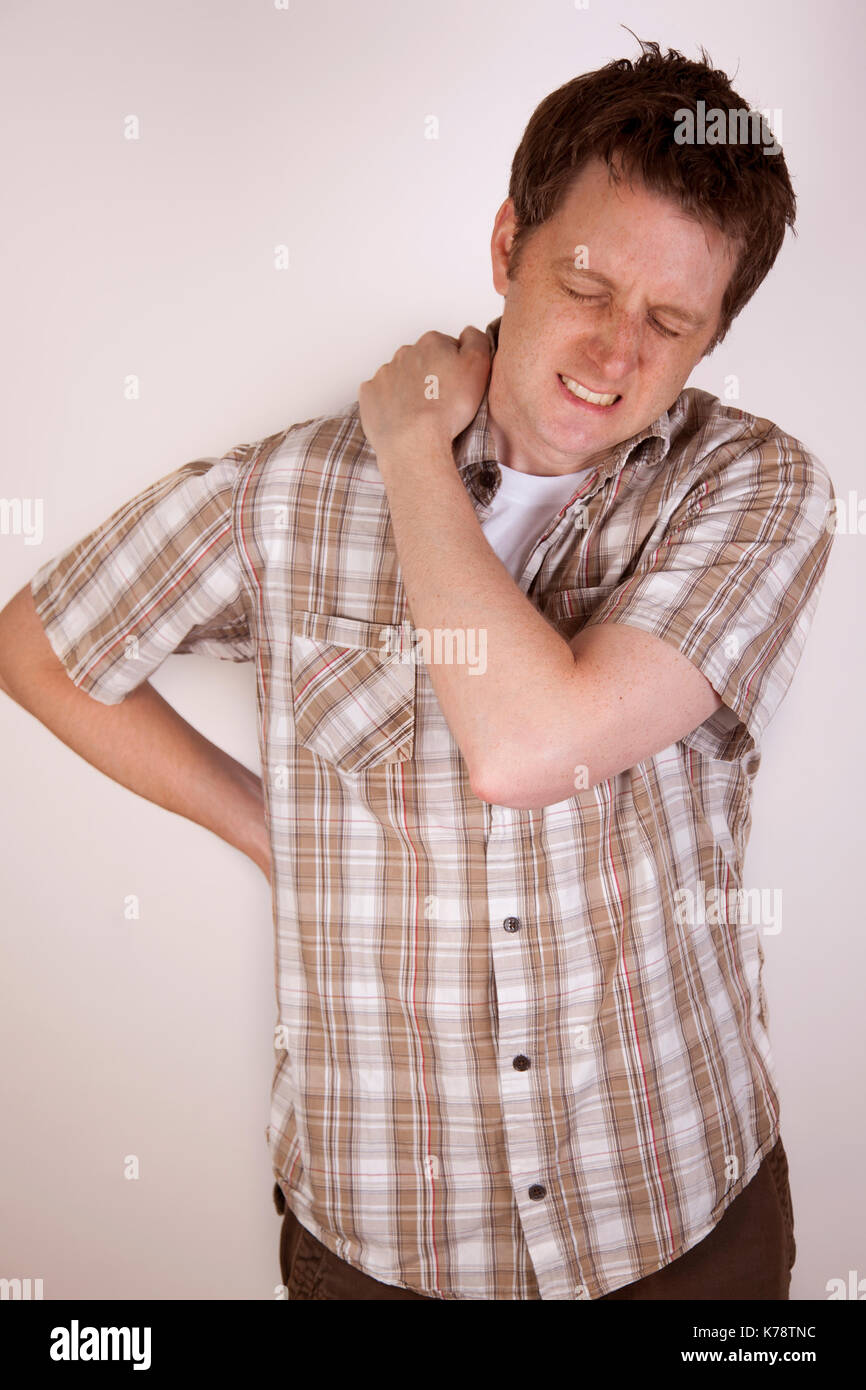 man holding his shoulder in pain - Stock Image