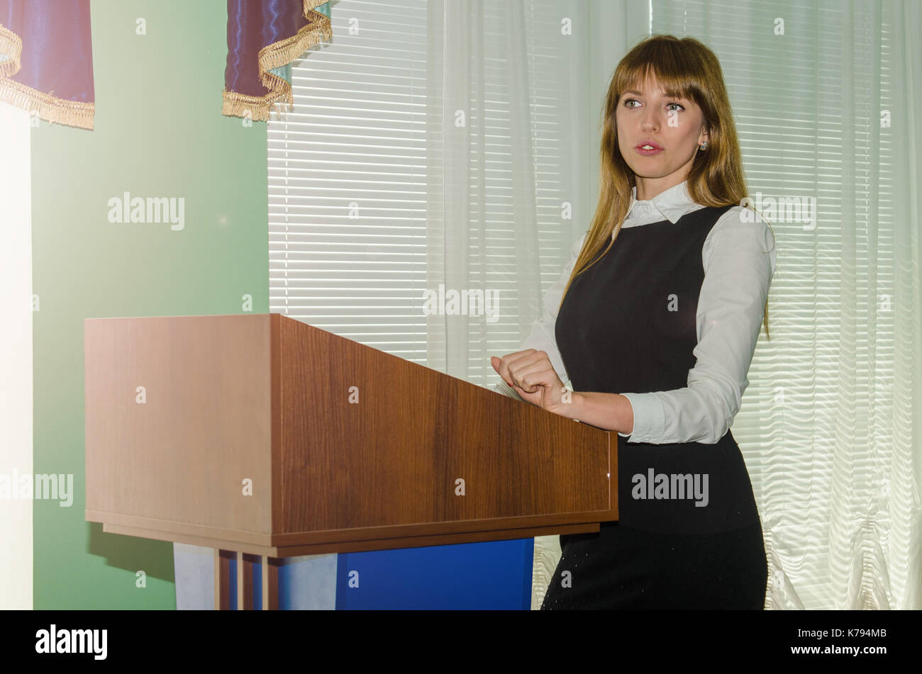 lecture of a young women behind the podium - Stock Image