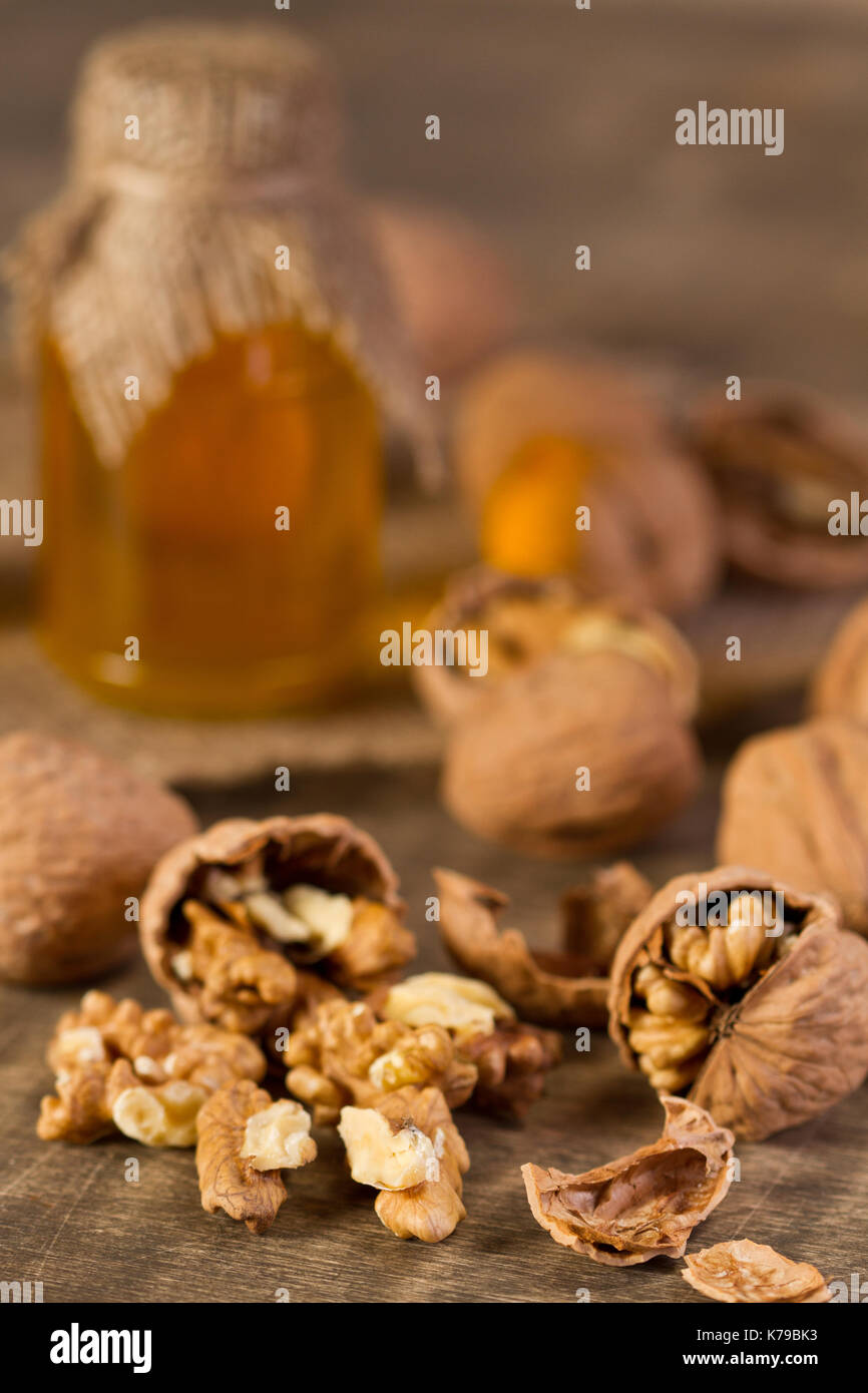 Walnuts and walnuts oil on old wooden table Stock Photo