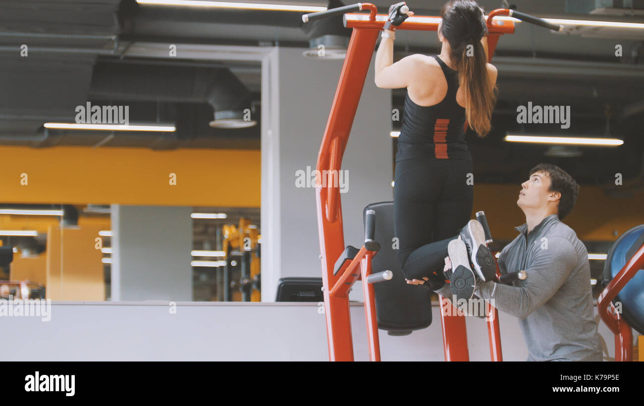 Fitness-club - young woman performs Pull-Ups with male coach - rear view, close up - Stock Image