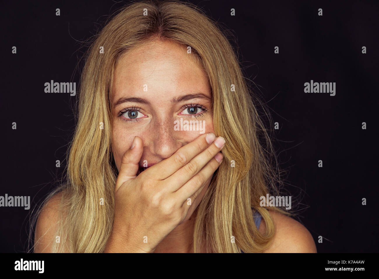 Young woman laughing with hand over mouth - Stock Image