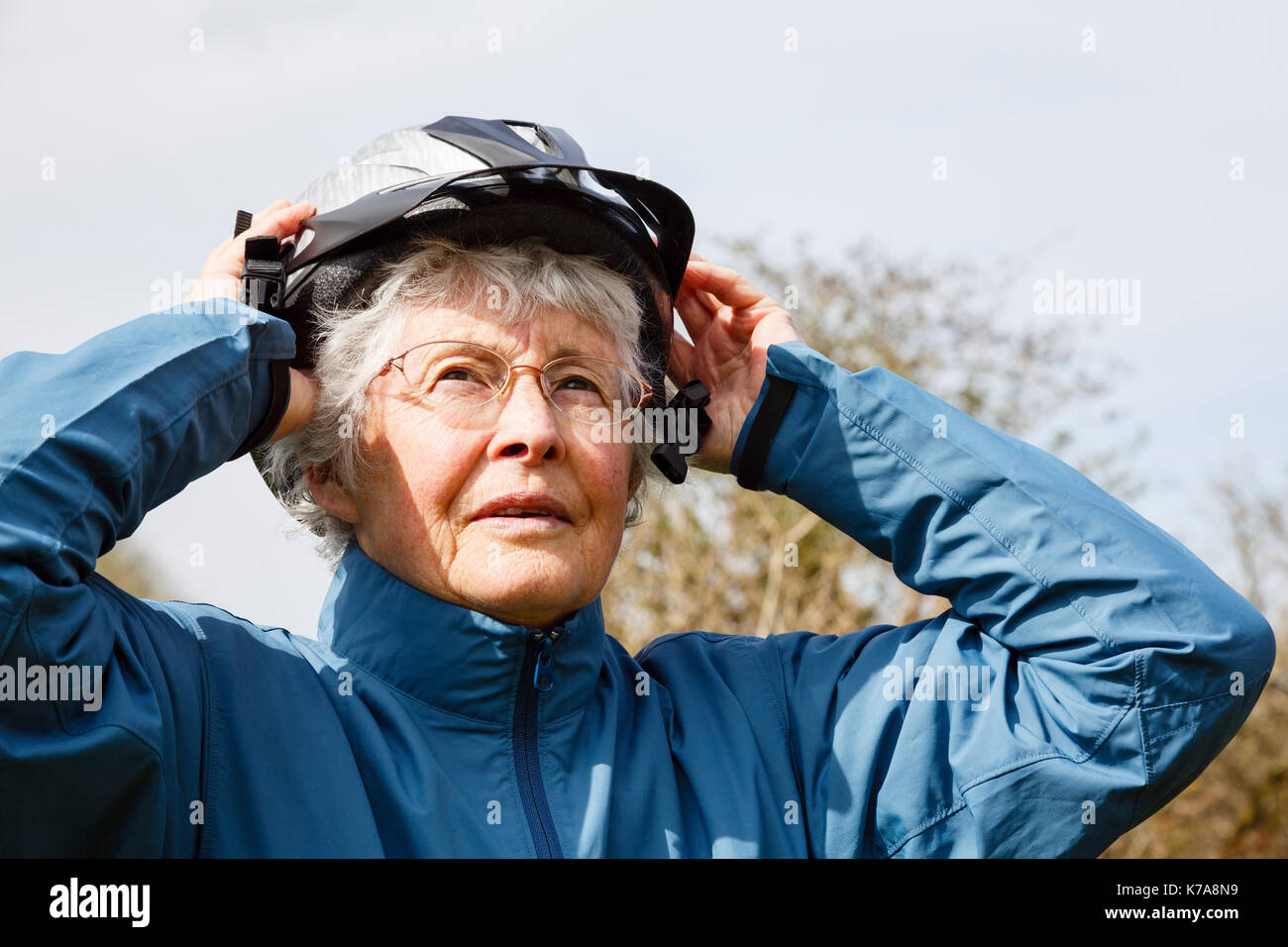 Active senior elderly woman retiree putting on a cycling helmet preparing to go for a cycle ride to keep fit in retirement. England, UK, Britain - Stock Image
