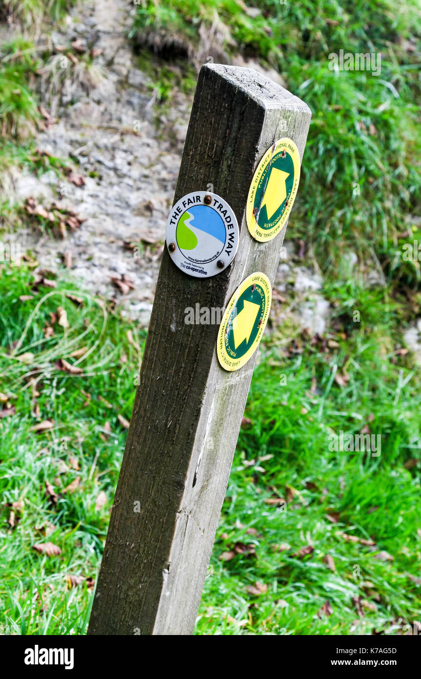 A wooden footpath way marker for The Fair Trade Way, English Lake District, Cumbria, England, UK - Stock Image
