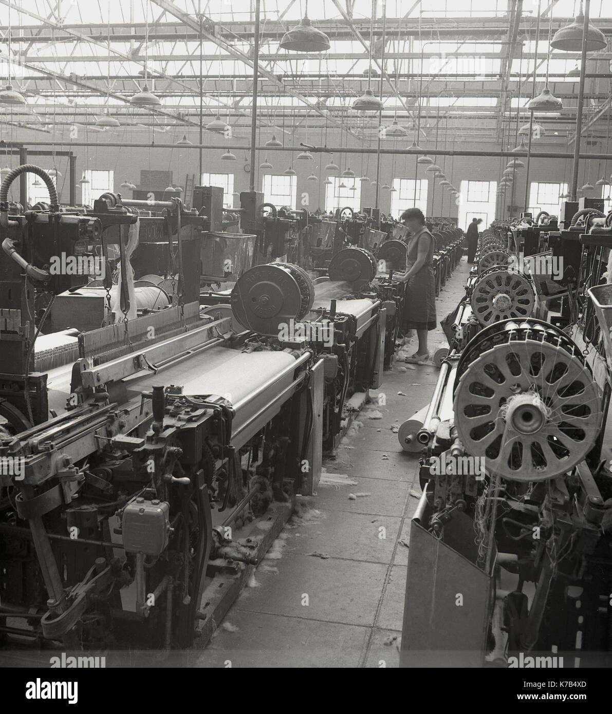 1950s, historical, Irish weavers, female workers standing on wooden floorboards using mechanised linen looms, Northern Stock Photo