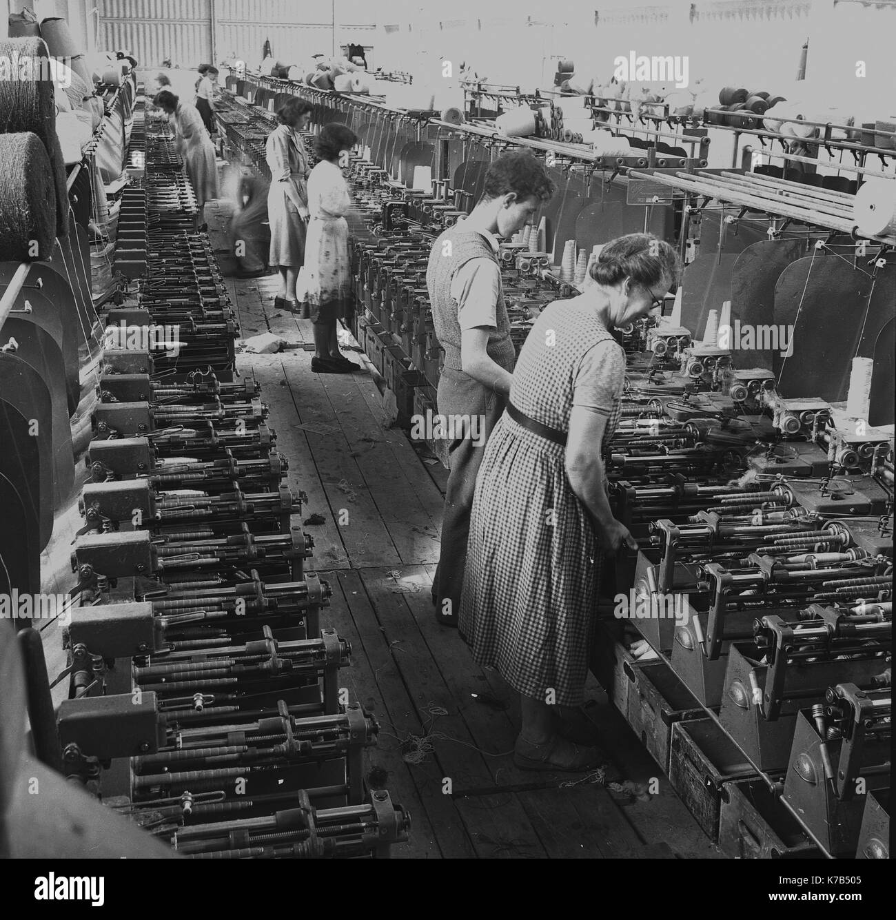 1950s, historical, Irish weavers, female workers standing on wooden floorboards using mechanised linen looms, Northern Ireland. - Stock Image