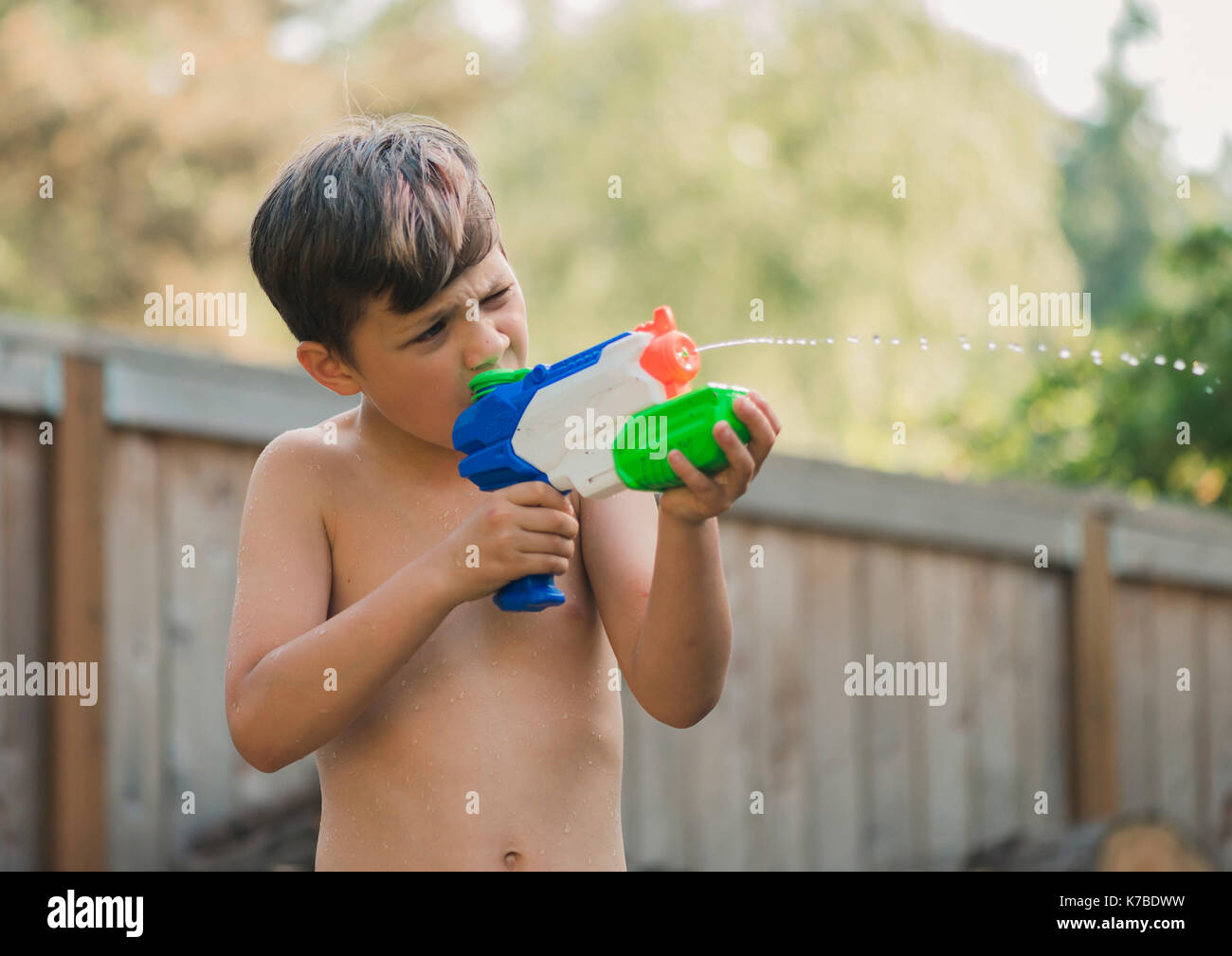 Boy aiming on something with squirt gun while standing in yard - Stock Image