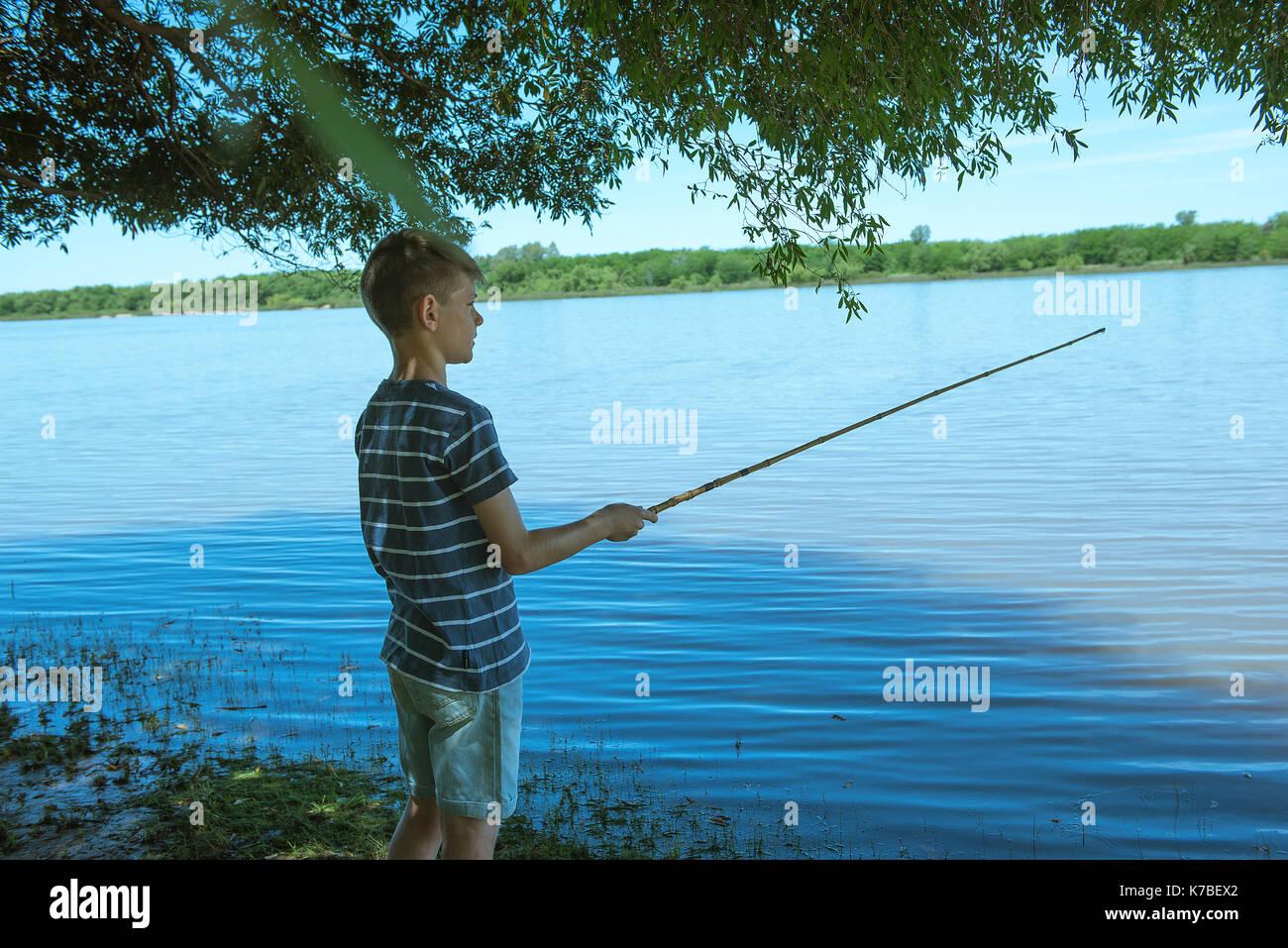 Boy fishing on lake shore - Stock Image