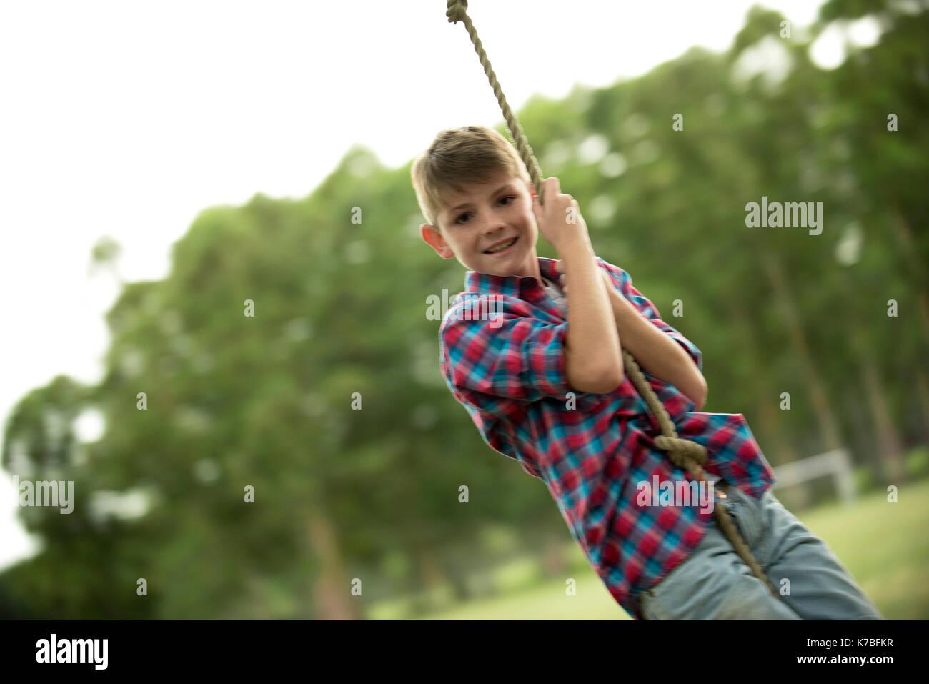 Boy swinging on rope - Stock Image